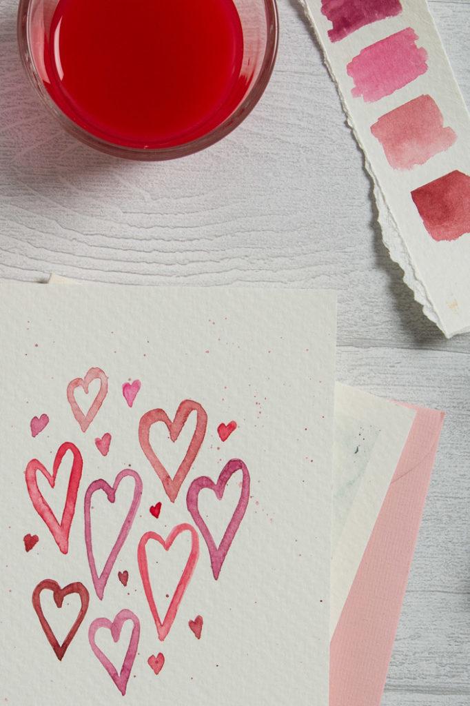 Selbst bemalte Aquarellkarte mit rosa Herzen