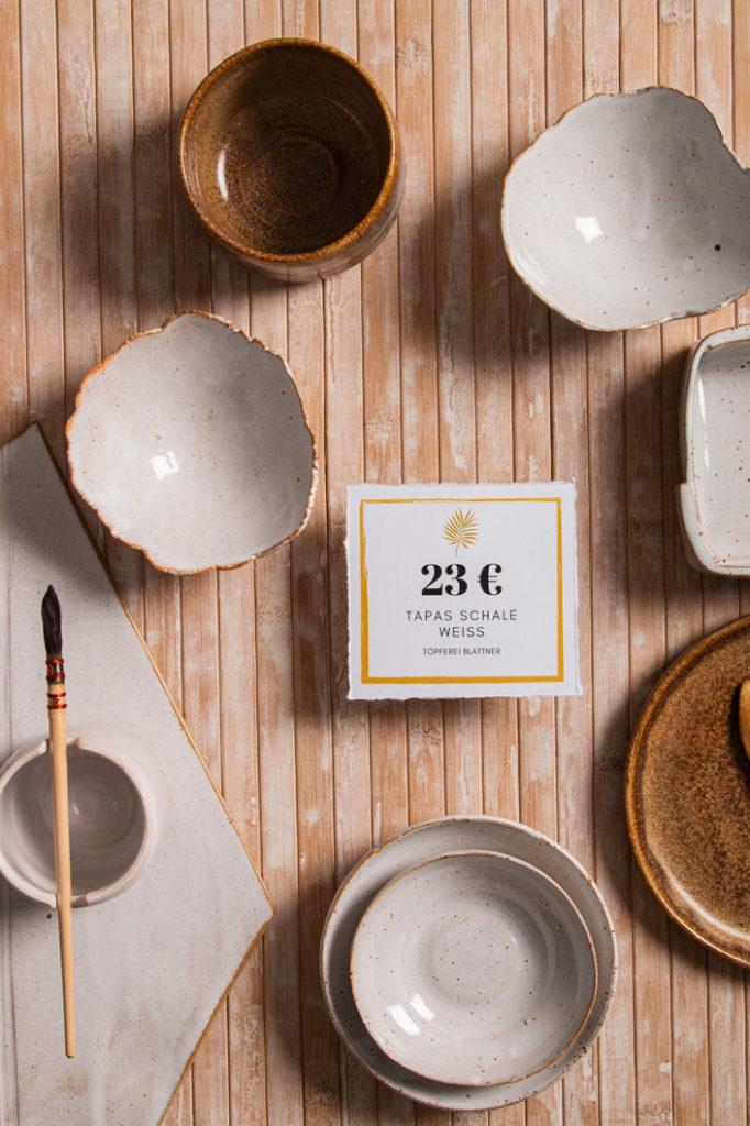 Flatlay getöpferter Schalen und Teller mit Preisschild aus Jupp Recyclingpapier.