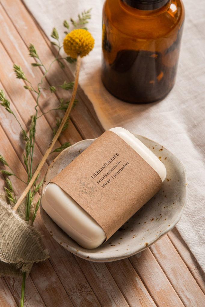 Seife in Banderole aus Kraftpapier. Genau wie die getöpferte Seifenschale fügt sich das Kraftpapier in die nachhaltige Gestaltung ein.