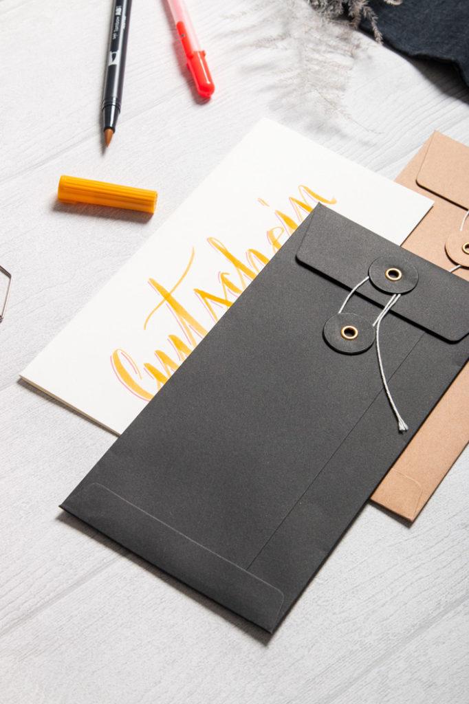 Bindfadenkuverts in den Farben Schwarz, Manila und Weiß  geben Ihrem Gutschein den passenden wertigen Rahmen.