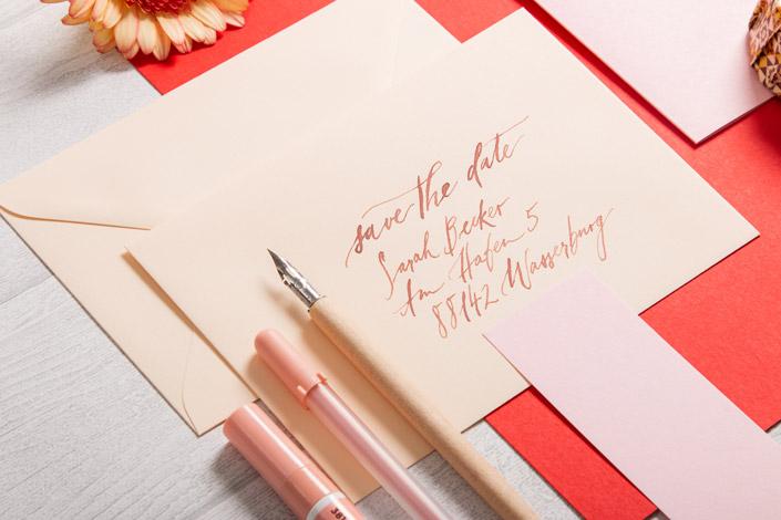 Vanillefarbene Kuverts mit kalligrafischer Beschriftung und hellrotem Papier