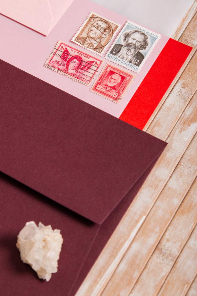 Detailfoto von Briefumschlägen in Weinrot mit rosa Papier und Briefmarken