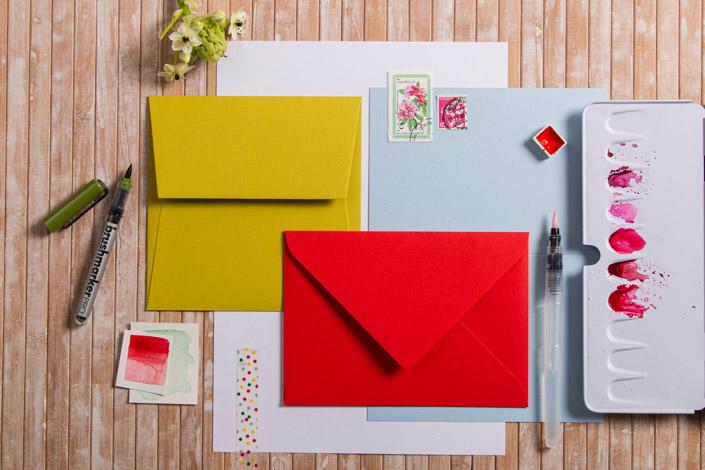 Umschläge und Papiere in den Farben Hellrot, Kiwigrün, Hellblau und Weiß