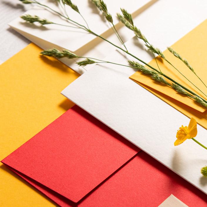 Flatlay aus Colorplan Kuverts in den Farben Bright Red und Citrine sowie einer Aquarellkarte