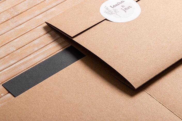 Detailaufnahme einer quadratischen Klappkarte aus Kraftpapier. Die Klappe ist mit einem Aufkleber verschlossen.