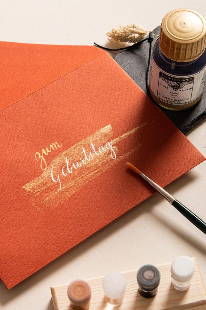 Rostfarbener Umschlag DIN B6 mit goldener und weißer Kalligrafie