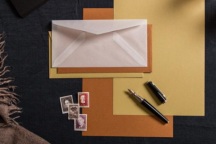 Flatlay einer Papeterie mit historischen Briefmarken und einem edlen Otto Hutt Füllfederhalter