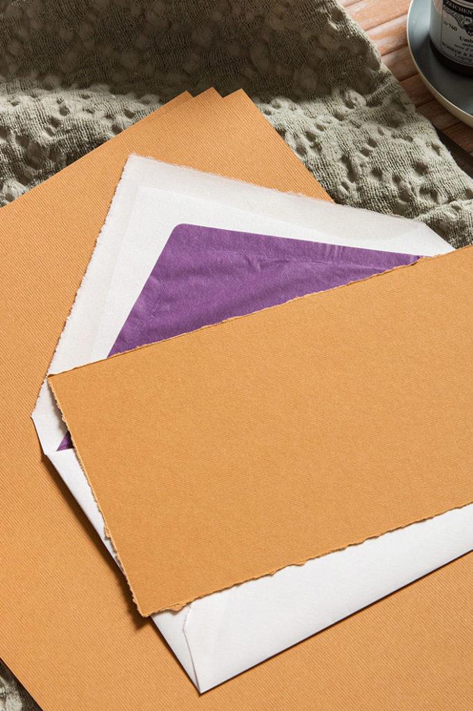 Strukturpapier in der Farbe Zimt zu weißen Büttenkuverts mit lila Seidenfutter