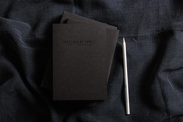 Aufsicht auf Black Box Papeteriesammlung und weißen Stift auf schwarzem Tuch.