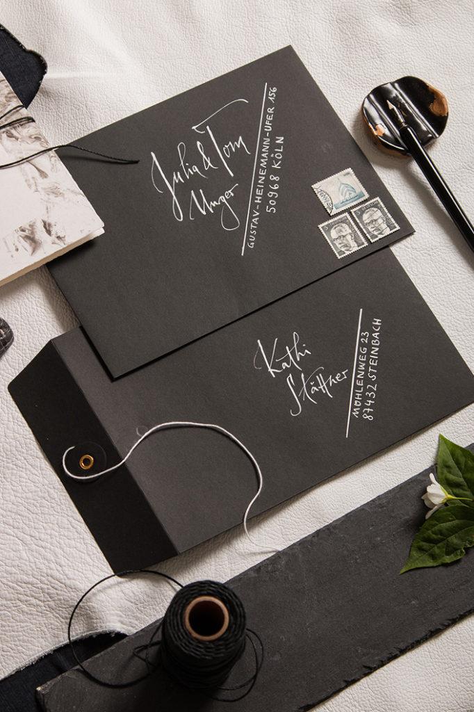 Mit weißer Kalligrafie beschriftete schwarze Briefumschläge mit Bindfadenverschluss