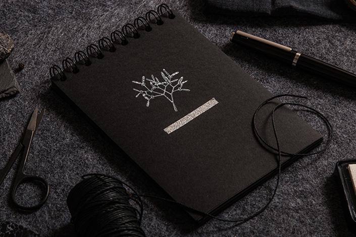 Blick aufs Black Friday Highlight: Schwarzers Colorbook Notizbuch mit weißem Stempelmotiv