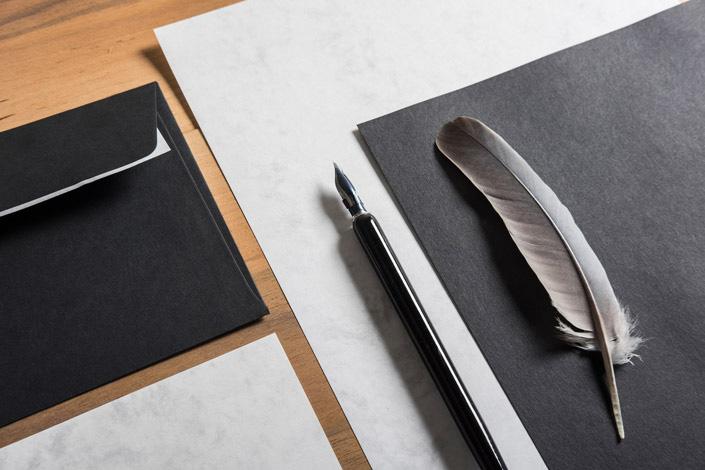 Eines unserer Black Friday Highlights: Schräge Aufsicht auf eine Papeterie mit dem schwarzen Papier und der DIN lang Hülle der Sorte Hot Colors