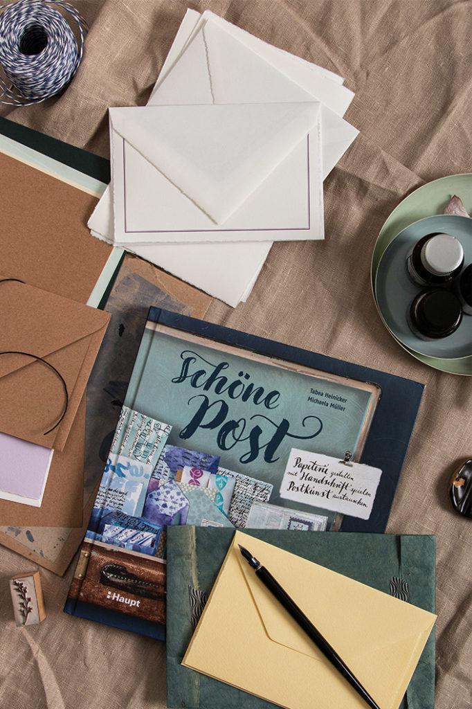 """Aufsicht auf das Postkunst Buch """"Schöne Post"""" von Micheala Müller und Tabea Heinicker. Dazu Kraftpapier und Büttenpapier, das auch im Buch genutzt wird."""