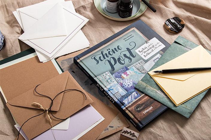 Schräge Aufsicht auf das Postkunst Buch von Micheala Müller und Tabea Heinicker. Dazu Kraftpapier und Büttenpapier, das auch im Buch genutzt wird.