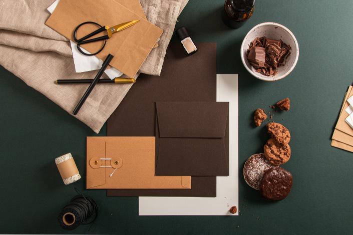 Aufsicht auf die Papeterie aus Colorplan Bitter Chocolate und Briefumschlägen mit Bindfadenverschluss und Schokoladenkekse