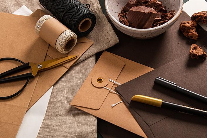 Papeterie aus dunkelbraunem Colorplan Papier und hellbraunen Briefumschlägen mit Bindfadenverschluss