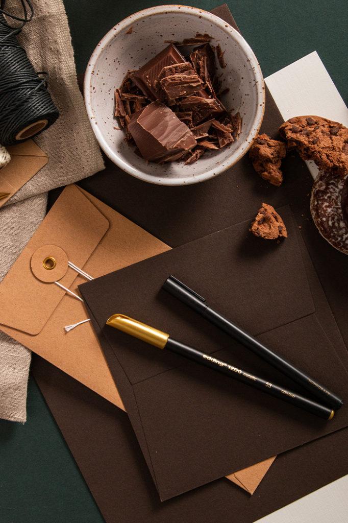 Dunkelbraunes Colorplan Papier im Foto mit Bindfadenhüllen, gebackenen Schokokeksen und Schokolade