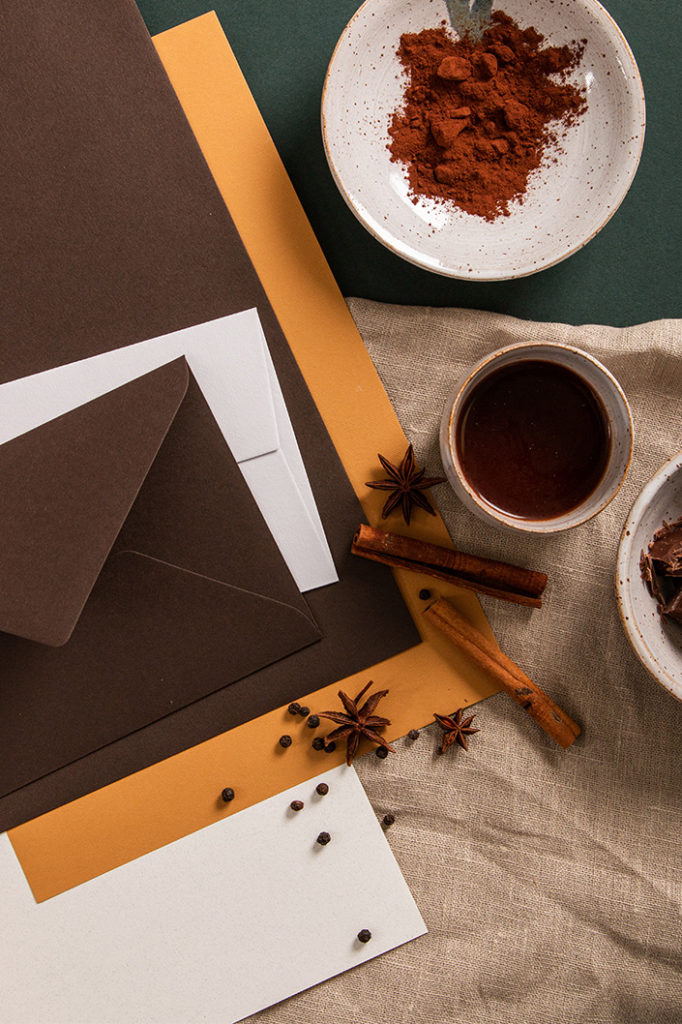 Hochformatiges Foto der Farbpalette um Colorplan Bitter Chocolate. Dunkelbrauner Briefumschlag und echtes Kakaopulver.