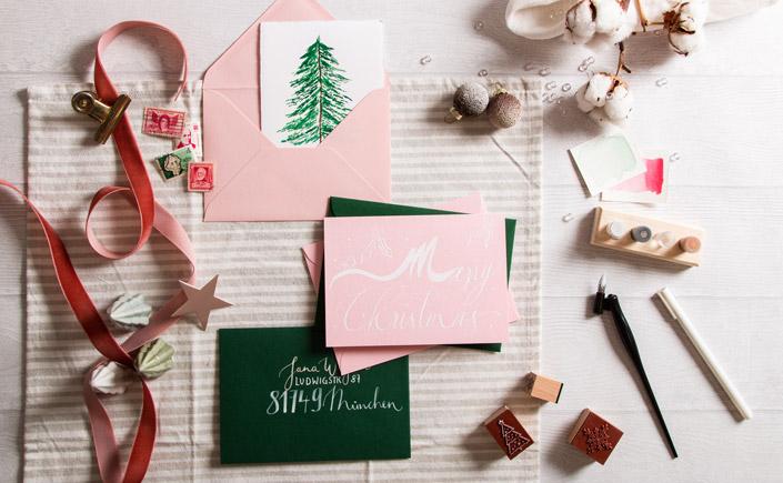Flatlay von Weihnachtskarten und Briefumschlägen mit Aquarellmotiv in Grün und Rosa