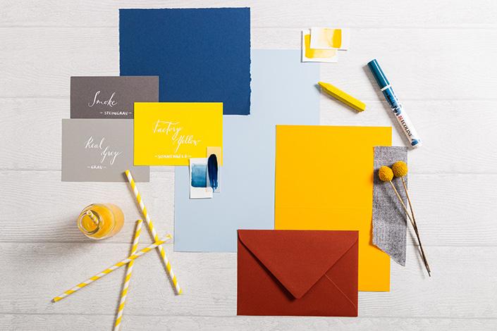 Papeterie Flatlay das den Mix aus Hot Colors Hellblau und den Farben des Jahres 2021 Gelb und Grau zeigt