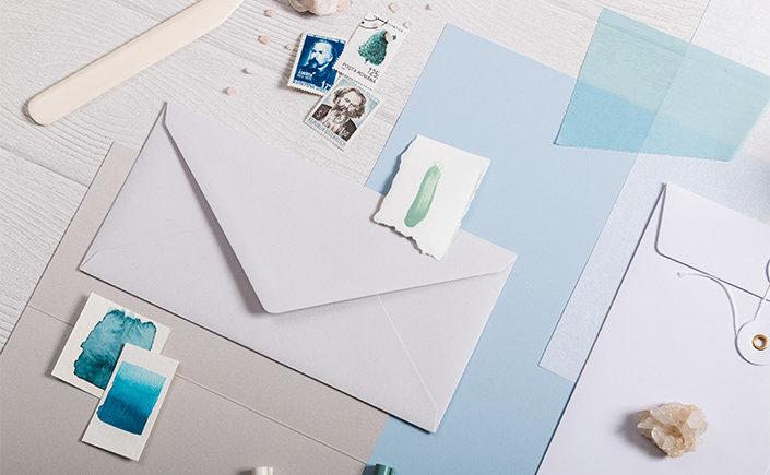 Nahaufnahme einer Briefhülle in einer Zusammenstellung von Schreibwaren und Papieren in einer hellblauen Farbpalette.