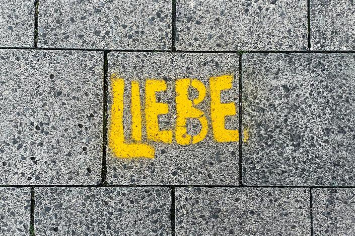 Moodbild Farbe des Jahres 2021: gelber Schriftzug auf grauen Pflastersteinen