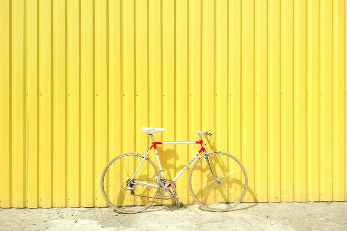 Moodbild Farbe des Jahres 2021: Retro Fixie Bike vor zitronengelber Blechwand