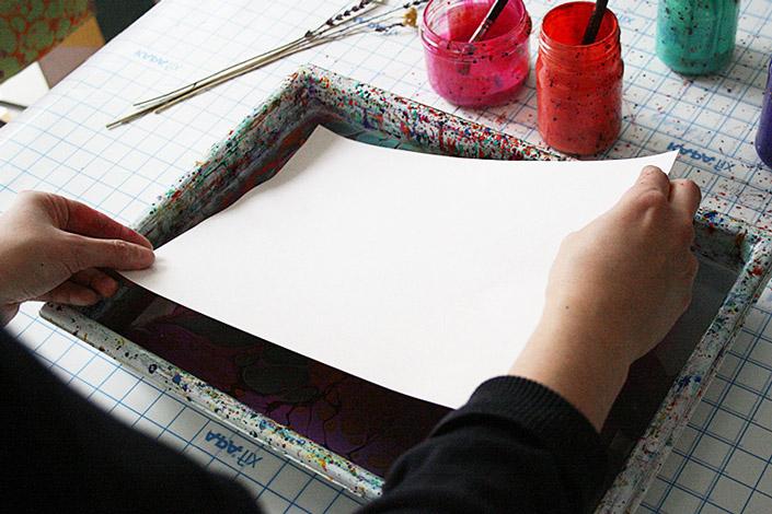 Karen platziert das Papier, das sie marmorieren möchte auf der mit Alaun behandelten Wasseroberfläche. Dadurch werden die Farben übertragen.