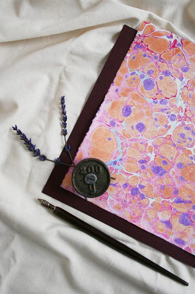 Hochformatiges Flatlay eines marmorierten Papiers. Wie man einfach Papier selbst marmorieren kann zeigt Karen im Papier Direkt Blog.
