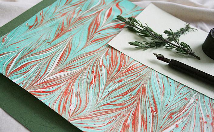 Marmoriertes Papier von Indigo Creaftroom im Flatlay mit Schreibfeder und Dekoration