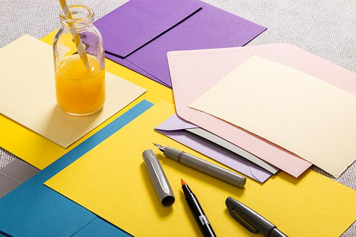 Briefumschläge in kräftigen Farben mit Papier in der Farbe Illuminating