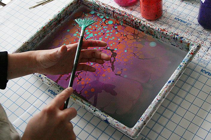 Papier selbst marmorieren. Karen zeigt, wie man das Marmorierbad vorbereitet und die Farbe aufbringt