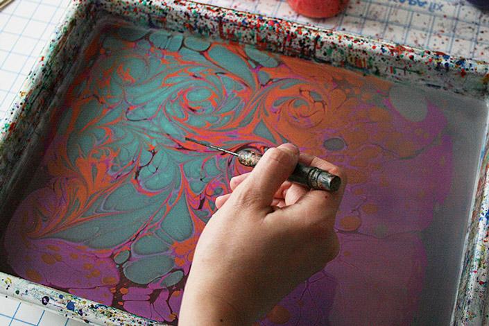 Hand mit Ahle über Marmorierbad. Karen formt mit der Ahle Muster in die bunte Farbe.