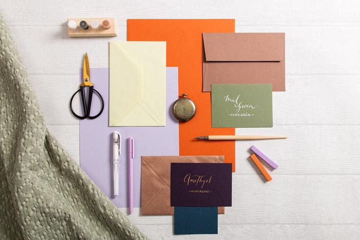 Aufsicht auf einen Papiermix in den Farben der Toskana. Im Zentrum stehen die Briefumschläge aus Büttenpapier in der Farbe Green Tea.