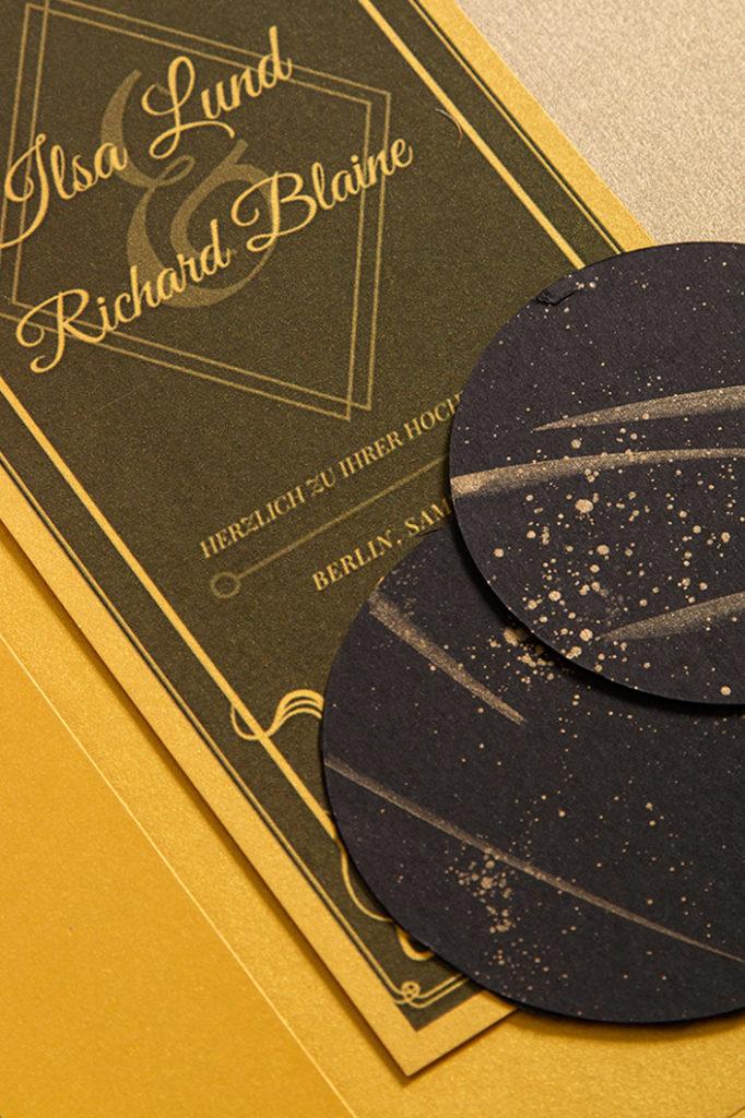 Einladungskarte aus goldenem Feinpapier und gold bemalten Anhängern