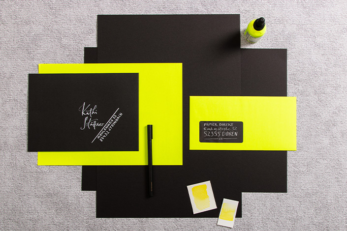 Gelbes Neonpapier und Umschläge mit schwarzem Fotokarton