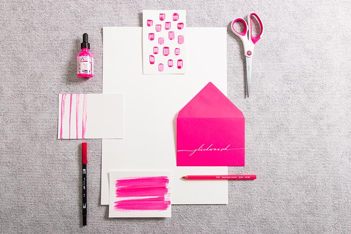 Neonpinke Briefumschläge zu weißen Postkarten mit Neontusche