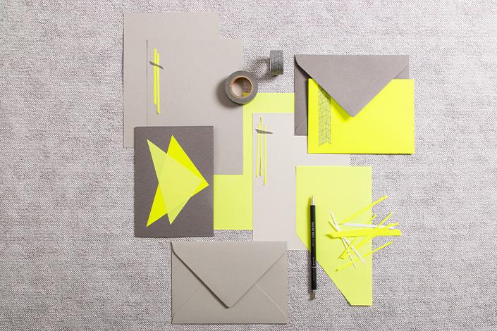 Neonpapier in Gelb mit grauen Karten und Briefumschlägen