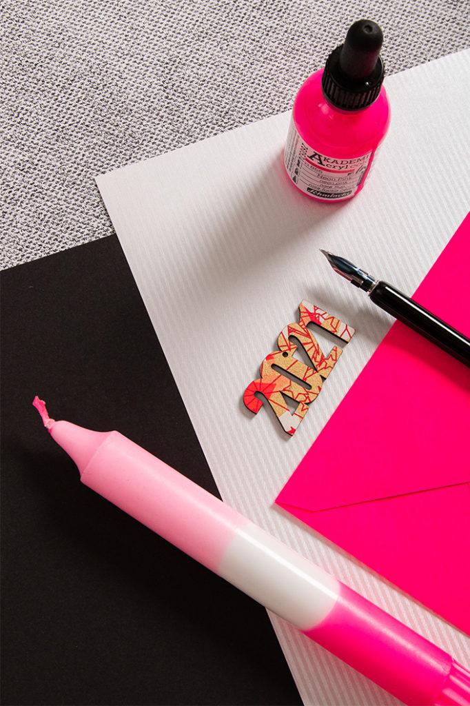 Neonpinke Umschläge zu silbernem und schwarzen Papier