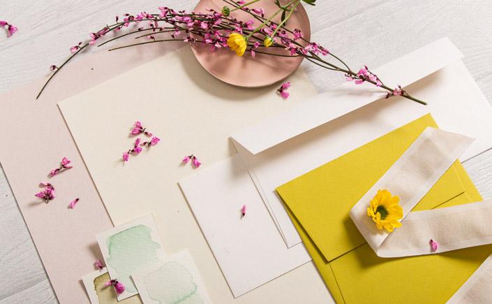 Farbpalette mit Papieren, Karten und Umschlägen in zarten Farben