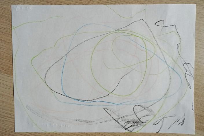 Aufsicht auf weißes BlattPapier mit Kinderzeichnung dass am Weltkindermaltag die Kritzelphase erklärt