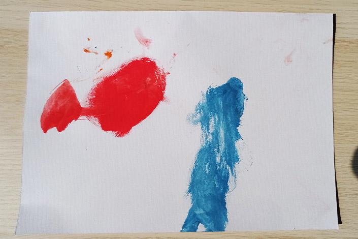 Kritzelzeichnung eines Kindes in den Farben Blau und Rot