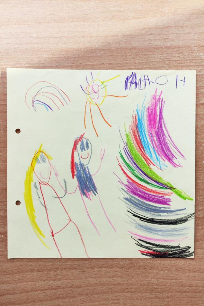 Kinderzeichnung von zwei Mädchen, der Sonne und Regenbogen.