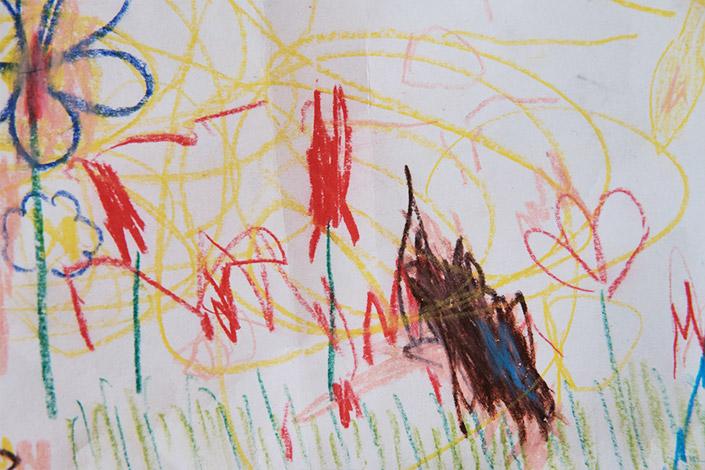 Kinderzeichnung, rote Blumen auf einer Blumenwiese eines 2-jährigen Kindes.