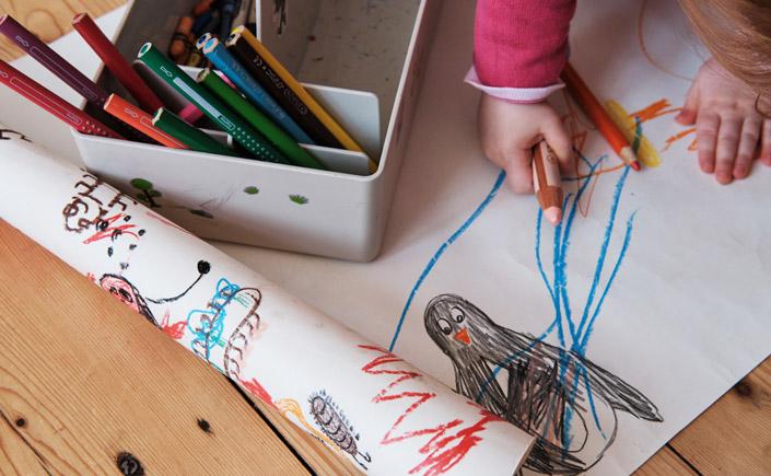 Kleinkind malt am Weltkindermaltag mit bunten Stiften auf Papier