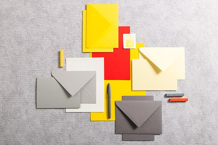 Papiere in der Farbe Factory Yellow zusammen mit Grautönen und Rot