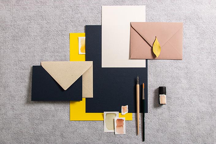 Papeterie in einer Farbpalette aus Dunkelblau, Chamois und Factory Yellow