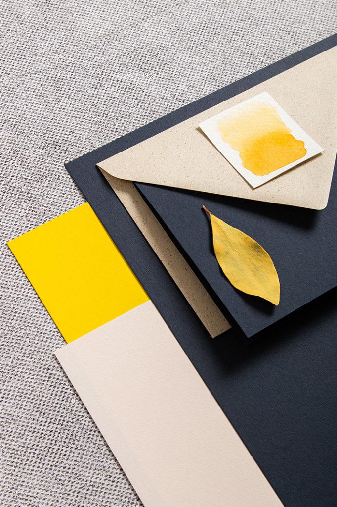 Farbpalette aus Papieren in Dunkelblau, Sonnengelb und Sand