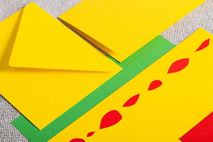 Papeterie aus gelbem Papier mit Akzenten in Rot und Grün.