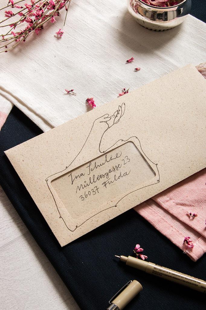 Briefumschlag aus Graspapier mit Illustration einer Hand. Empfänger und Versender reichen sich die Hand.